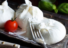 Italian cheese burrata. With tomatoe and basil on a dark background stock photos