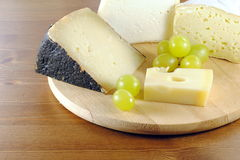 Italian cheese with grapes on wooden cutting board. Italian cheese made of cow and sheep milk, with green grapes Stock Images