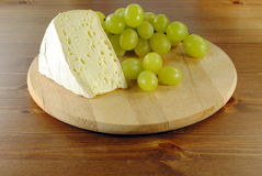 Italian cheese with grapes on wooden cutting board. Italian cheese made of cow milk, with green grapes Royalty Free Stock Image