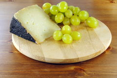 Italian cheese with grapes on wooden cutting board. Italian cheese made of sheep milk, with green grapes Royalty Free Stock Photography
