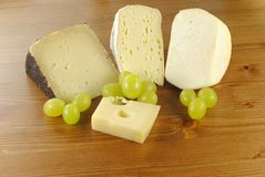 Italian cheese with grapes on wooden table Stock Photos