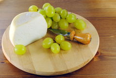 Italian cheese with knife and grapes. On wooden cutting board, make with sheep milk Royalty Free Stock Images