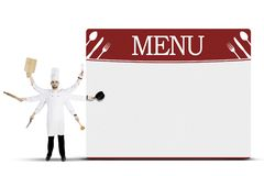 Italian chef with kitchen utensils and board menu. Portrait of Italian man chef is holding kitchen utensils with many hands while standing near a menu board royalty free stock photos