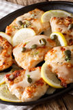 Italian chicken piccata with sauce, lemon and capers close-up. V Stock Photos