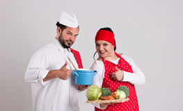 Italian Chief cook in Red Apron and Handsome Cook are Showing Nu. Italian Chief cook and Handsome Dark Hair Cooky are Showing Number One Sign Royalty Free Stock Photo