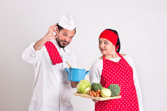Italian Chief cook in Red Apron Shows OK Sign. Italian Chief cook Shows OK Sign and  Handsome Dark Hair Cooky is Looking at Him Royalty Free Stock Photography