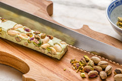 Italian Christmas sweets. Traditional Italian Christmas sweets with pistachios on wooden cutting board and knife Royalty Free Stock Photography