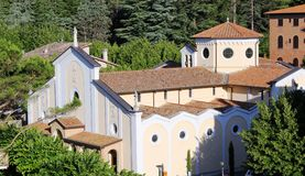 Italian Church surrounded by woods. A view of a Church in a small town in Tuscany, Italy.  The church is bathed in sunshine and surrounded by woods Royalty Free Stock Photo