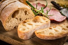 Italian ciabatta bread cut in slices with salami. Stock Images