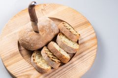 Italian ciabatta cut in slices on a wooden plate. Homemade bread with a knife. Stock Images