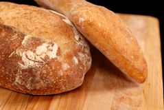Italian and Ciabatta loaves of bread. On cutting board royalty free stock photography