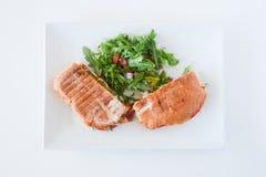 Italian ciabatta panini sandwich with chicken and tomato. On a white plate Stock Image