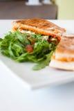 Italian ciabatta panini sandwich with chicken and tomato. On a white plate Stock Photo