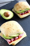 Italian ciabatta sandwich. With salami, cheese and avocado on wooden background Royalty Free Stock Photo