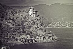 Italian Coast of the Ligurian Sea. Portofino, Italy. A building on top of a rock. Antique white and black Royalty Free Stock Photo