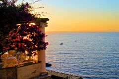 Italian coast sunset. View from Sorrento, Italy at dusk from a flower draped terrace Royalty Free Stock Image