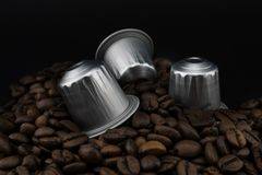 Italian coffee capsules or coffee pods on coffee beans, black background royalty free stock photos