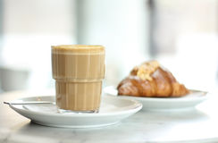 Italian Coffee with fresh croissant. An Italian coffee sat on a white plate with a fresh croissant out of focus in the background Royalty Free Stock Image