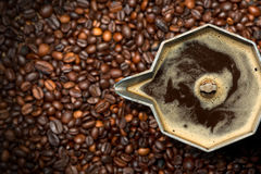 Italian Coffee Maker with Coffee Beans. Closeup of an old italian coffee maker moka pot - top view with roasted coffee beans on background stock photography