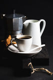 Italian coffee set for breakfast. Cup of hot espresso, creamer with milk, cantucci and moka pot on dark rustic wooden Stock Photos