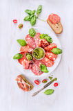 Italian cold meat plate with bread, basil pesto and tomatoes Stock Photos