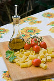 Italian cooking ingredients. Pasta,tomatos,olive oil and basil Royalty Free Stock Photography