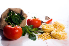 Italian cooking ingredients on a white marble tabletop. Italian cooking ingredients on a white marble counter top Royalty Free Stock Photo