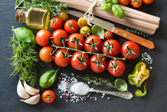 Italian cooking ingridients : cherry tomatoes, herbs, pasta and Royalty Free Stock Photos