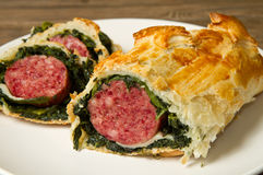 Italian cotechino in crust with spinach Royalty Free Stock Photo