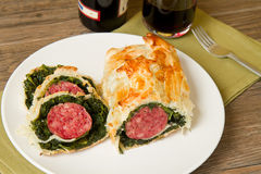 Italian cotechino in crust with spinach Royalty Free Stock Image