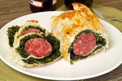 Italian cotechino in crust with spinach Stock Image