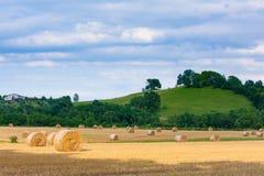 Italian countryside panorama. Round bales on wheat field Stock Photos