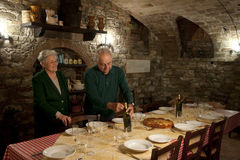Italian couple opening wine at dinner table Royalty Free Stock Image