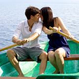 Italian couple on wood boat rowing and kissing Stock Images