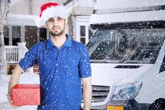 Italian courier holding a Christmas gift at outdoor Royalty Free Stock Photos
