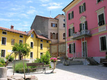Italian courtyard. Colorful Italian courtyard, with pink and yellow buildings and pink geraniums. Rocca Grimalda, Piedmont, Italy royalty free stock photography