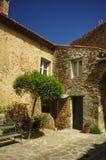 Italian courtyard. Countryside. Tree, windows, wall, bench Stock Photos