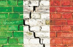 Italian crisis concept image: Italy national flag painted on a cracked grungy brick wall. Italy national flag painted on a cracked grungy brick wall. Concept stock photo
