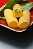 Italian cuisine. Rigattoni with basilicum on red plate Stock Image