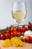 Italian cuisine. Symbolic arrangement of the Italian cuisine - pasta, garlic, tomatoes and white wine in a glass Royalty Free Stock Image