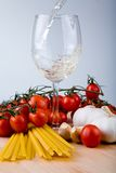 Italian cuisine. Symbolic arrangement of the Italian cuisine - pasta, garlic, tomatoes and white wine being poured into a glass Stock Photos