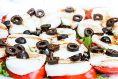 Italian cuisine background. Italian salad caprese with sliced olives. Soft focus on foreground and background royalty free stock images