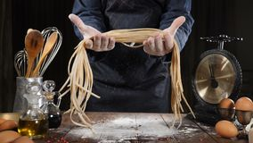 Italian cuisine concept. Chef holding just-made pasta above wood board ,kitchen utensil around, all made from semolina. Flour. Cooking homemade pasta. Slow stock footage