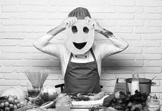 Italian cuisine concept. Cook with hidden face in uniform. Sits by table with vegetables and kitchenware. Man holds rolled dough with cut smiley face on white royalty free stock images