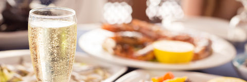 Italian cuisine. Glass of prosecco and variety of seafood. Shallow DOF, banner royalty free stock photo