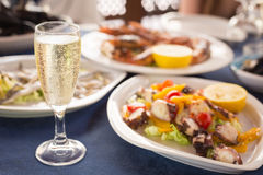 Italian cuisine. Glass of prosecco and variety of seafood Royalty Free Stock Photos