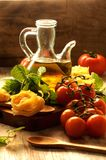 Italian cuisine ingredients olive oil, raw pasta, tomatoes, Royalty Free Stock Photo