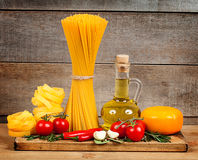 Italian cuisine. Pasta, a bottle of oil, tomatoes, spices Royalty Free Stock Images