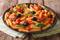Italian cuisine: pasta penne with meatballs, olives and tomatoes Stock Images