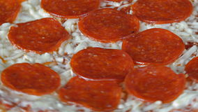 Italian Cuisine: Pepperoni Pizza Slowly Turning in Display. Italian Cuisine: Delicious pepperoni pizza with mozzarella cheese slowly turning featuring a melted stock video footage